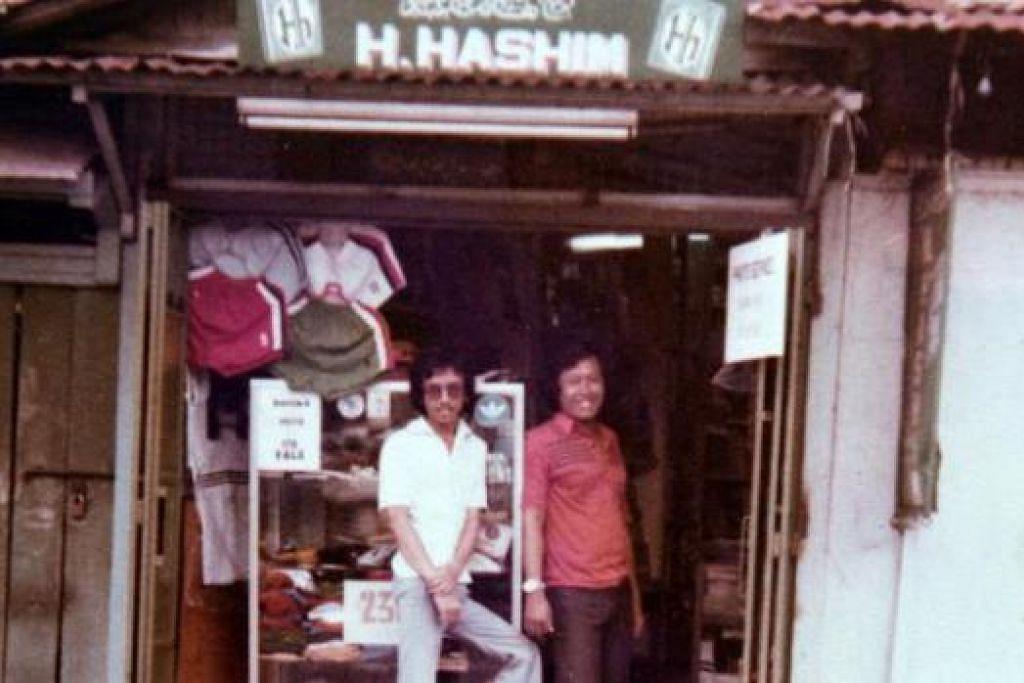 TIDAK DITELAN ZAMAN: Gambar yang diambil sekitar 1970-an ini menunjukkan Haji Abdul Aziz (kiri) berdiri di depan kedai datuknya itu di Geylang. – Foto HAJI HASHIM