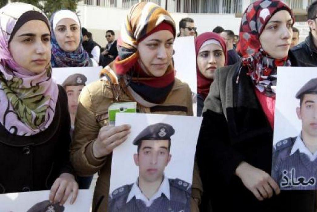 HARAPAN HAMPA: Cik Anwar Tarawneh (tengah), isteri juruterbang Jordan yang telah dibakar militan IS, memegang gambar suaminya dalam satu rapat pada 3 Februari lalu di ibu kota Amman, bagi menuntut pembebasan beliau. - Foto AFP