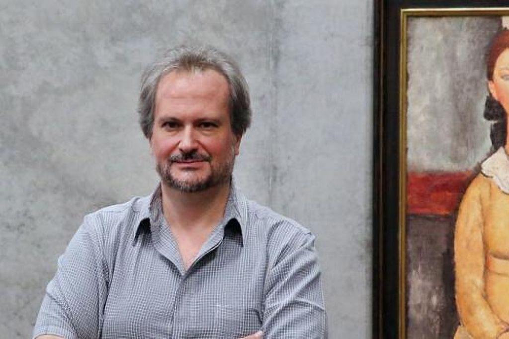 PENGASAS MUZIUM PERANCIS: Ahli sejarah seni Encik Marc Restellini dengan lukisan artis dari Italy, Amedeo Modigliani, yang akan dipamerkan di sebuah muzium seni Perancis, Singapore Pinacotheque de Paris. - Foto fail