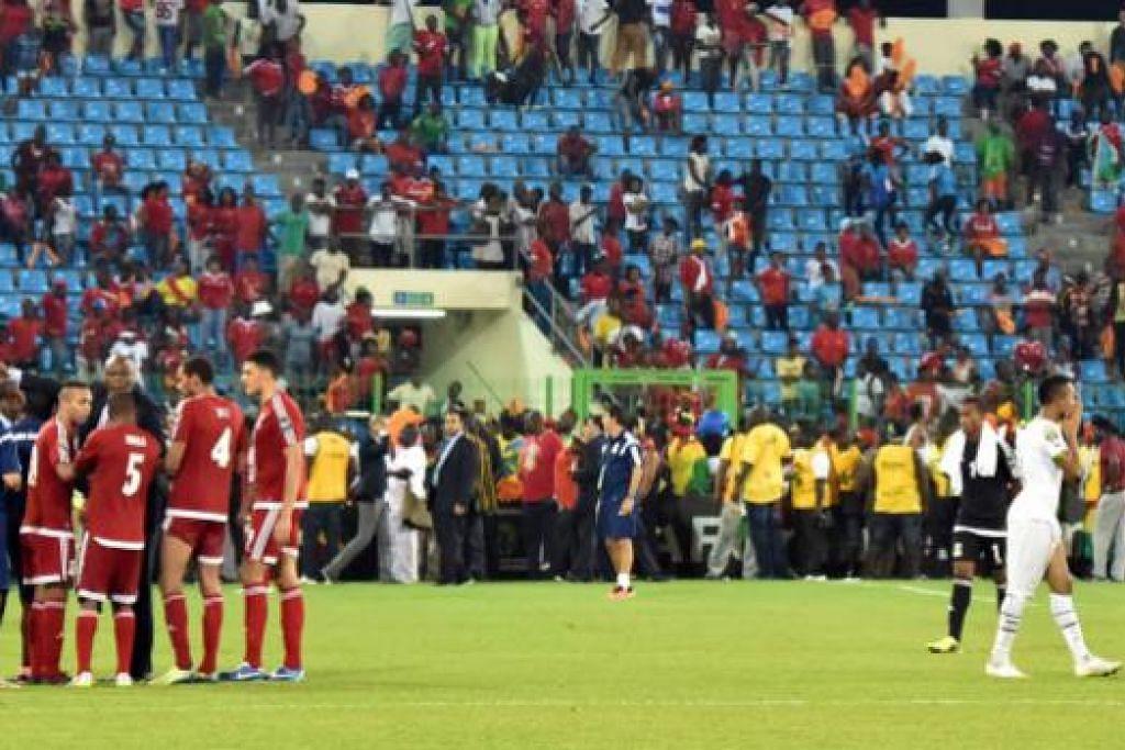 TERGENDALA: Pemain Ghana (jersi putih) dan Equitorial Guinea terpaksa menanti di padang selepas pengadil menghentikan permainan.