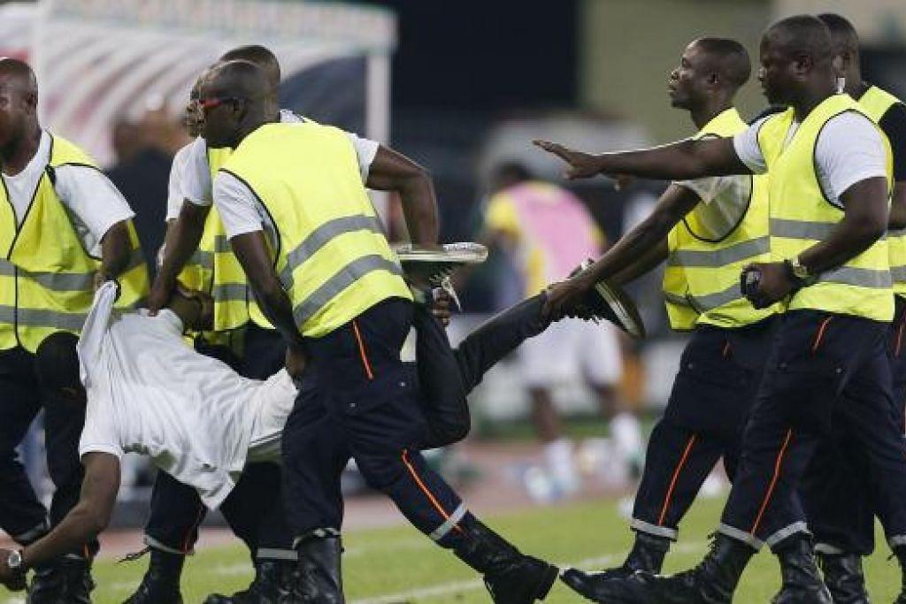 BUAT KACAU: Seorang penyokong Equitorial Guinea yang mencerobohi padang diheret keluar oleh polis.