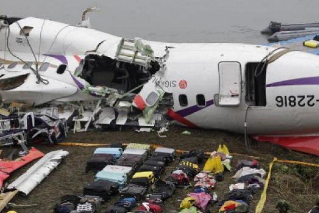 BEG PENUMPANG: Beg-beg penumpang yang ditemui bertaburan dan terapung dekat bangkai pesawat TranAsia Airways yang terhempas kelmarin dikumpulkan di depan pesawat tersebut. - Foto REUTERS