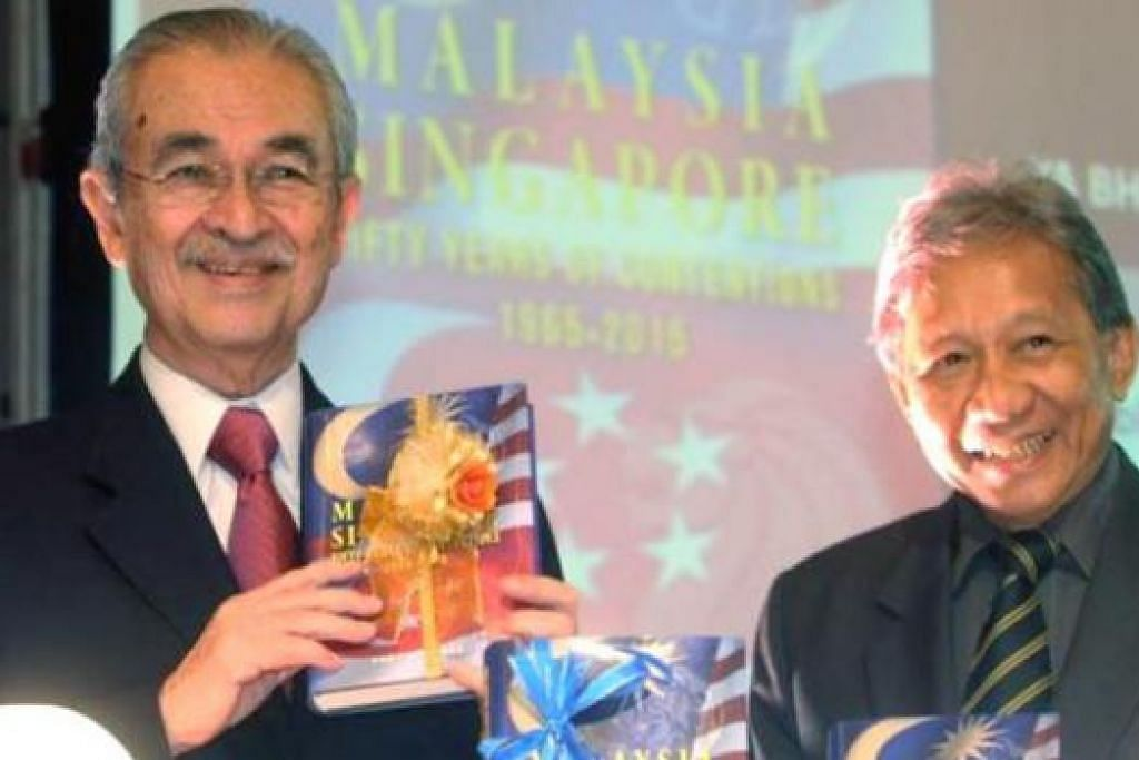 LANCARKAN BUKU: Tun Abdullah (kiri) melancarkan buku Malaysia-Singapore, 'Fifty Years of Contentions 1965-2015' oleh Tan Sri Abdul Kadir (kanan). - Foto THE STAR