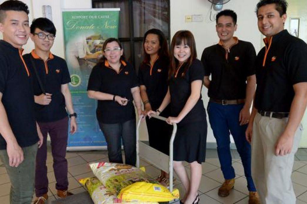 KERJA AMAL: Pekerja Lagun Sari bersama habuan yang diberikan kepada penghuni Rumah Tumpangan Warga Tua Jamiyah (Darul Takrim) di Tampines. - Foto TUKIMAN WARJI