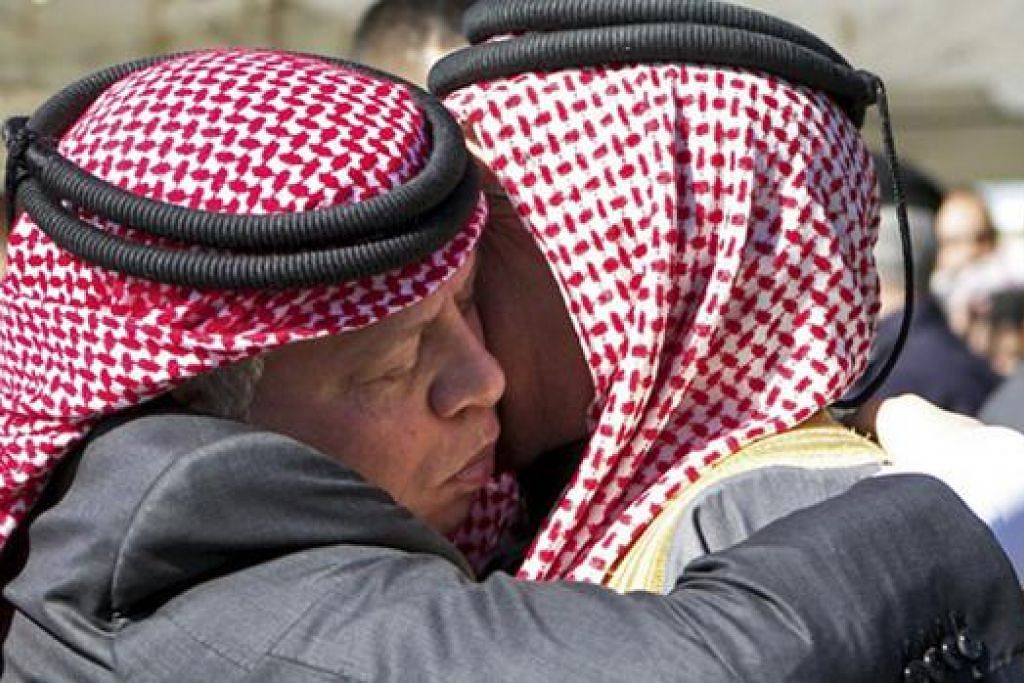 SALAM TAKZIAH: Raja Abdullah (kiri) menawarkan takziahnya kepada Encik Safi al-Kasaesbeh, bapa juruterbang Jordan, Leftenan Mouath al-Kasaesbeh, di rumah keluarga al-Kasaesbeh di bandar selatan Karak. - Foto-foto REUTERS