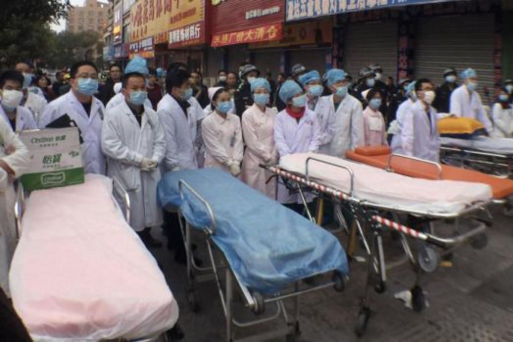 SIAP HULURKAN BANTUAN: Kakitangan perubatan dengan katil beroda bersiap sedia memberikan pertolongan cemas kepada mangsa kebakaran di pusat beli-belah di daerah Huidong.