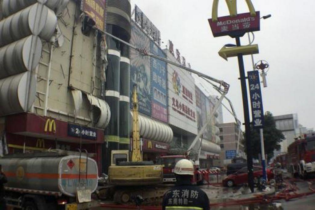 TEMBOK DIPECAHKAN: Para anggota bomba terpaksa membuat lubang di tembok bangunan pasar raya bagi menyelamatkan mangsa-mangsa yang terperangkap dalam kebakaran di pusat beli-belah di daerah Huidong ini. - Foto-foto REUTERS