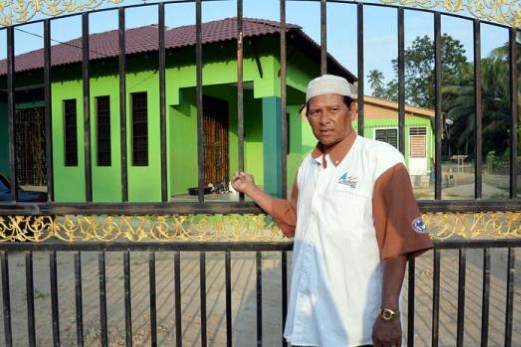 SUBKONTRAKTOR BINA RUMAH MEWAH: Encik Mat Zain Harun, 58 tahun, yang pernah bekerja sebagai tukang kayu selama 10 tahun di tapak binaan termasuk bagi membina flat di Geylang Serai, berdiri megah di depan empat rumah banglo yang telah siap dibinanya di Kampung Pondok Berangan, Kelantan.