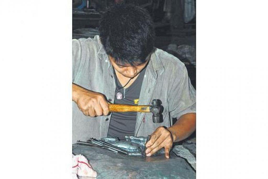 HASIL KREATIF: Tukang perak di pekarangan kuil Wat Srisuphan sibuk mengukir perak.