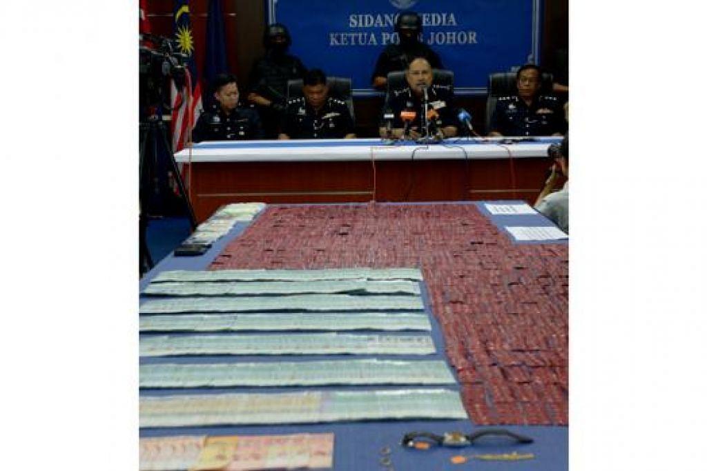 HASIL KERJASAMA DUA NEGARA: Ketua Polis Johor, Datuk Mohd Mokhtar Mohd Shariff (duduk dua dari kanan), berkata kejayaan menumpaskan sindiket dadah rentas sempadan Rabu lalu adalah hasil kerjasama agensi-agensi penguatkuasaan Singapura dan Malaysia. - Foto TUKIMAN WARJI