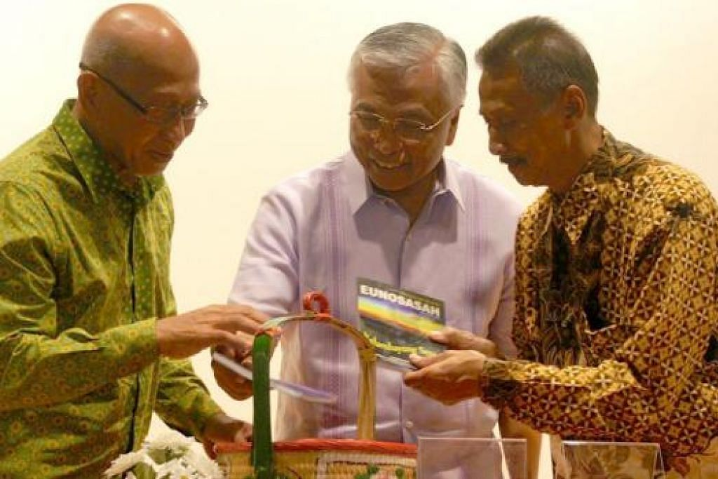 DILANCARKAN: Encik Sumadi (kiri) dan Encik Eunos (kanan) menunjukkan buku mereka kepada tamu terhormat majlis pelancaran di Perpustakaan Daerah Jurong 31 Januari lalu, Encik Hawazi. - Foto ihsan MOHD NAIM DAIPI