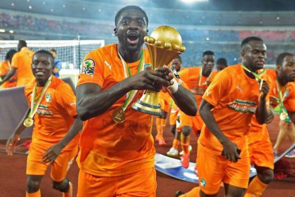 NIKMAT KEMENANGAN: Koule Toure (dua dari kiri) menjulang Piala Negara- Negara Afrika yang kini kembali ke Ivory Coast buat pertama kali sejak 1992. - Foto AFP
