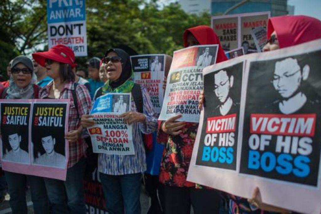 REAKSI PENYOKONG: Penyokong Encik Mohd Saiful Bukhari Azlan, bekas pembantu yang mendakwa diliwat Anwar Ibrahim, berkumpul di luar Mahkamah Persekutuan. - Foto AFP