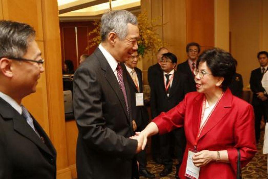 PERLINDUNGAN KESIHATAN SEJAGAT JADI TUMPUAN: Perdana Menteri Lee Hsien Loong bersalaman dan berbual mesra dengan Ketua Pengarah Pertubuhan Kesihatan Sedunia (WHO), Dr Margaret Chan, sambil disaksikan Menteri Kesihatan, Encik Gan Kim Yong (kiri), serta sebahagian ketua perwakilan sedunia yang berkumpul sempena acara dua hari Mesyuarat Menteri-Menteri Mengenai Perlindungan Kesihatan Sejagat: Cabaran Pasca 2015, di Grand Copthorne Waterfront Hotel, semalam. - Foto THE STRAITS TIMES