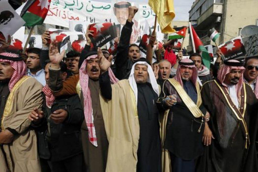 KEMAMPUAN JORDAN: Dapatkah Jordan mengatasi ancaman IS dalam jangka masa yang terdaya? Hal ini bergantung pada sokongan Dunia Arab dan Barat kepadanya, terutama kepimpinan Raja Abdullah. Para penunjuk perasaan Jordan memegang kain rentang yang memaparkan gambar Raja Abdullah dan Leftenan Muath al-Kasaesbeh dalam satu perarakan di Amman Jumaat lalu. - Foto REUTERS