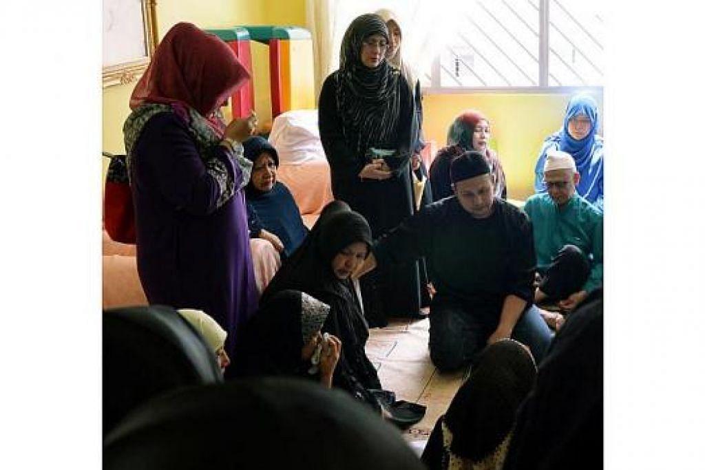 BERSEDIH: Keadaan sedih menyelubungi anggota keluarga Allahyarham Muhamad Nasron. Isteri Allahyarham, Cik Rohani (memegang sapu tangan), sukar menahan sebak di dada. Ibu Allahyarham, Ustazah Safiah Talib (bertudung biru gelap); bapa Allahyarham, Haji Anang (berkopiah putih); dan adik Allahyarham, Encik Muhamad Nauruz; kelihatan sugul. – Foto KHALID BABA
