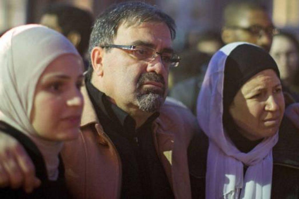 KELUARGA MALANG: Encik Namee Barakat bersama isteri, Cik Layla (kanan), dan anaknya, Cik Suzanne selepas tiga ahli keluarga mereka ditembak mati kelmarin. - Foto REUTERS