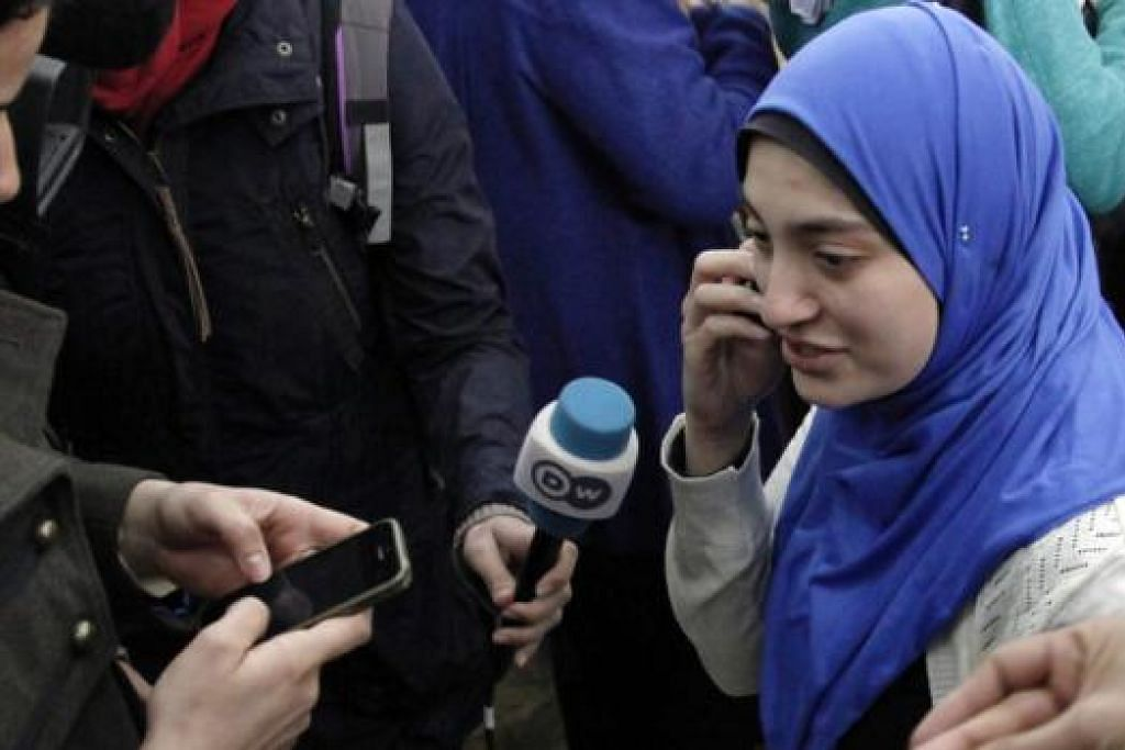 GEMBIRA: Cik Marwa Omara, tunang Encik Mohamed Fahmy, bercakap dengan wartawan di mahkamah semalam manakala Cik Jihan Rashed (gambar atas), isteri Encik Baher Mohamed, menghubungi keluarganya sebelum bercakap dengan wartawan. - Foto-foto REUTERS