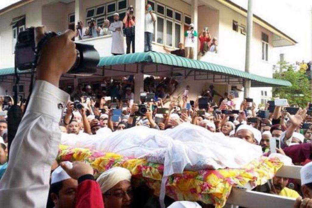 PENGHORMATAN TERAKHIR: Ribuan orang menziarahi jenazah Allahyarham Mursyidul Am PAS, Datuk Nik Abdul Aziz Nik Mat, di rumahnya sebelum jenazahnya dibawa ke Tanah Perkuburan Islam Pulau Melaka di sini, semalam. - Foto-foto UTUSAN ONLINE