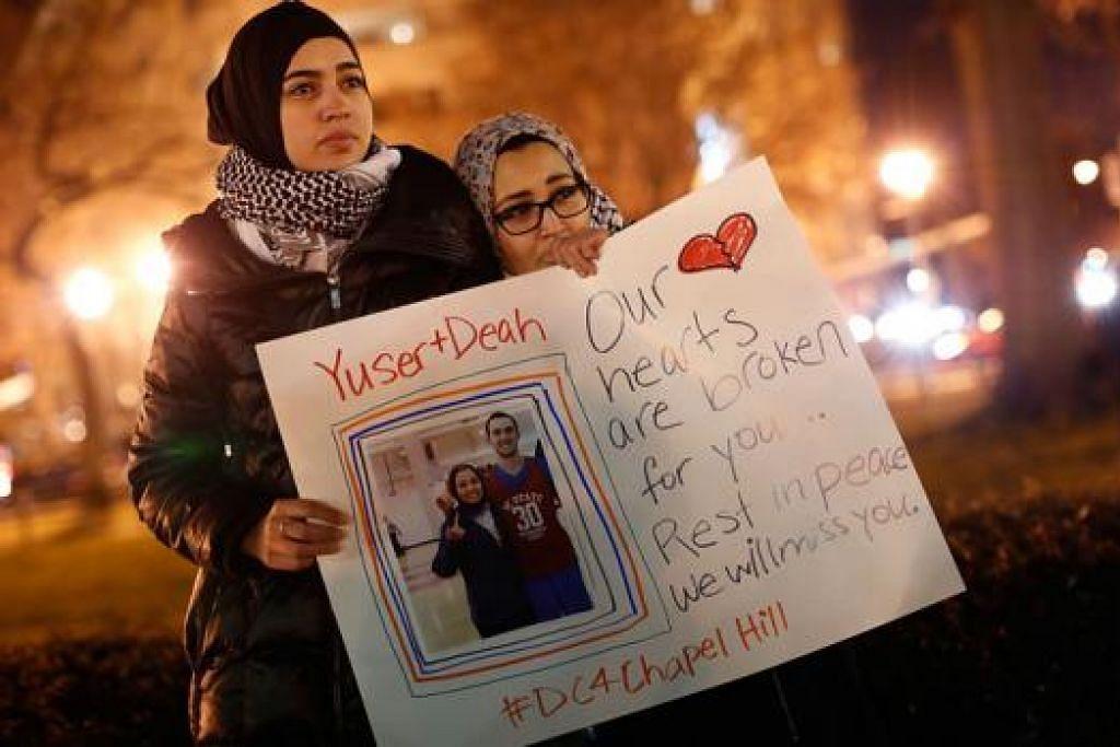 BERI SOKONGAN: Cik Kheira Benkreira (kiri) dan Cik Hasnia Bekkadja memberi sokongan sewaktu perhimpunan di Washington semalam sebagai memperingati tiga pelajar Muslim yang ditembak mati oleh jiran mereka. - Foto AFP