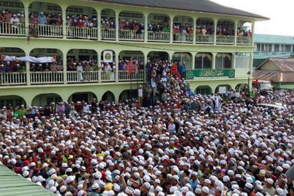 DIIRINGI RIBUAN ORANG: Ribuan penyokong dan orang ramai menyertai upacara pengebumian Allahyarham Datuk Nik Abdul Aziz Nik Mat di Kota Bharu pagi semalam. - Foto UTUSAN ONLINE