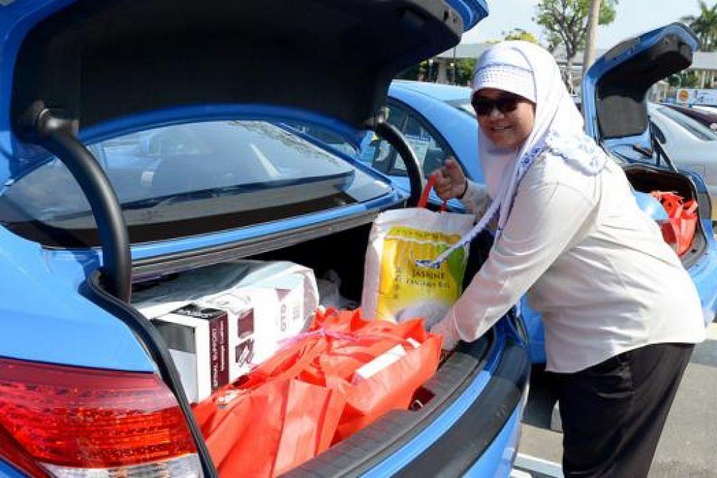 TOLONG GOLONGAN SUSAH: Cik Zainon Mohamed antara pemandu teksi yang secara sukarela menghantar habuan.