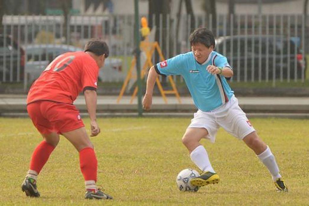 MASIH BOLEH LARI DENGAN BOLA: Kim Song (jersi biru) menunjukkan bahawa beliau masih mampu menggelecek bola apabila berdepan pemain lebih muda dalam satu perlawanan amal di Padang sempena pelancaran bukunya pada 24 Januari lalu.