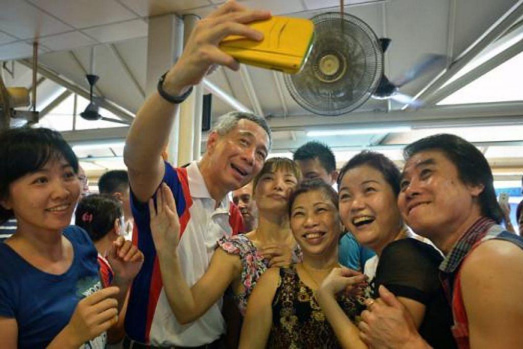 BERGAMBAR DENGAN PM: PM Lee mengambil 'we-fie' bersama beberapa penjaja di sebuah kedai kopi berdekatan pasar dan pusat makanan BlK 409 di Ang Mo Kio semalam. – Foto THE STRAITS TIMES