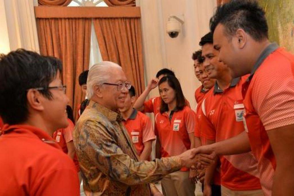 DAPAT PERHATIAN PRESIDEN: Presiden Tony Tan Keng Yam berbual sambil bersalaman dengan dua tekong sepak takraw Team Singapore, Muhammad Danial Feriza Padzli (kanan) dan kapten Mohamad Farhan Amran (di sebelahnya), dalam majlis yang diadakan di Istana petang kelmarin. - Foto THE STRAITS TIMES