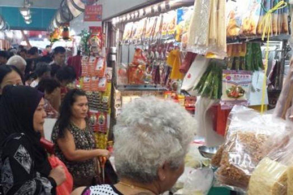 CEPAT HABIS: Peniaga di pasar di Toa Payoh ini mendapati sayur-sayur begitu laris. Ramai yang membelinya untuk disimpan di dalam peti ais dan kemudian dimasak semasa cuti umum nanti.