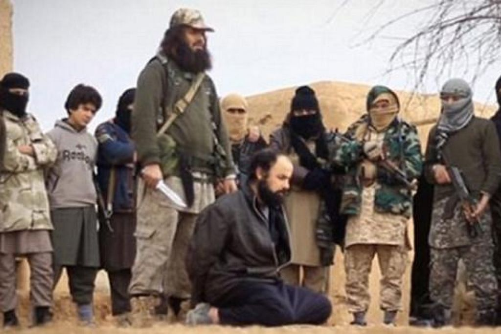 PENGGAL KEPALA: Militan IS yang berasal dari Sydney, Khaled Sharrouf yang kini berjambang dan berambut panjang (memegang pisau), telah menyembelih seorang lelaki yang didakwanya sebagai pengintip. - Foto DAILY MAIL
