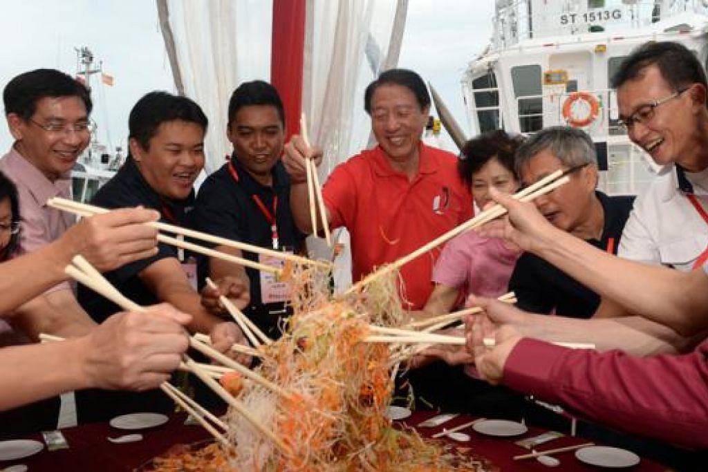 RAI TAHUN BARU CINA: Encik Teo (tengah) dan isteri (berbaju merah jambu) meluangkan masa untuk sesi lo hei dengan para pekerja pelabuhan selepas melawat mereka di PSA Marine. - Foto THE STRAITS TIMES