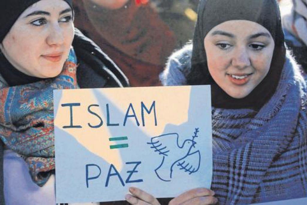 ISLAM ITU DAMAI: Dua Muslimah memegang mesej yang bermaksud 'Islam = Keamanan' dalam satu rapat di Madrid, pada 11 Januari lalu. - Foto REUTERS
