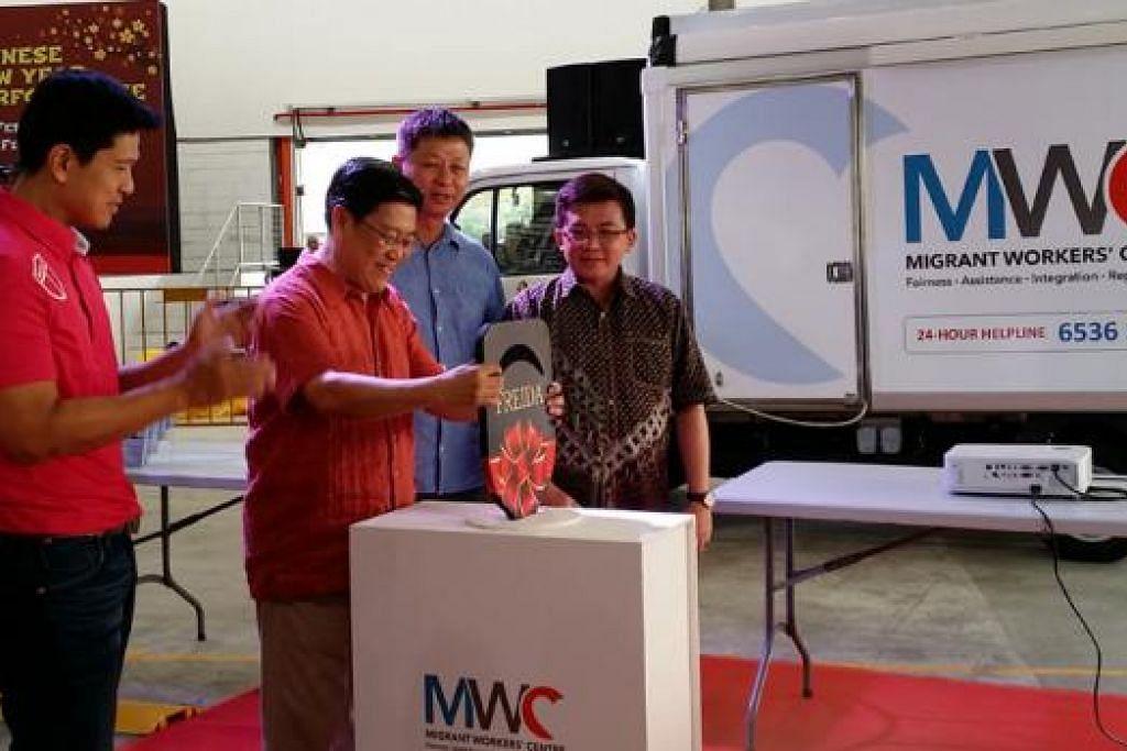 PELANCARAN FREIDA: Pengerusi Pusat Pekerja Asing (MWC), Encik Yeo Guat Kwang (memegang kunci) melancarkan pejabat mudah alih pertama MWC yang turut dikenali sebagai 'Forward Response, Engagement & Intel Deployment Asset' (FREIDA). - Foto MWC