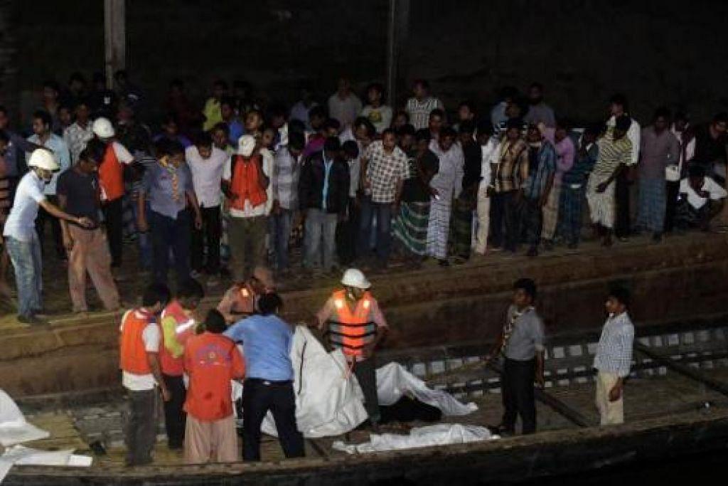 MAYAT DITEMUI: Pekerja penyelamat Bangladesh menemui mayat mangsa feri karam di Sungai Padma, kira-kira 70 kilometer ke utara Dhaka, kelmarin. Orang ramai memenuhi tebing kerana ingin tahu dan menyaksikan operasi mencari dan menyelamatkan. - Foto AFP