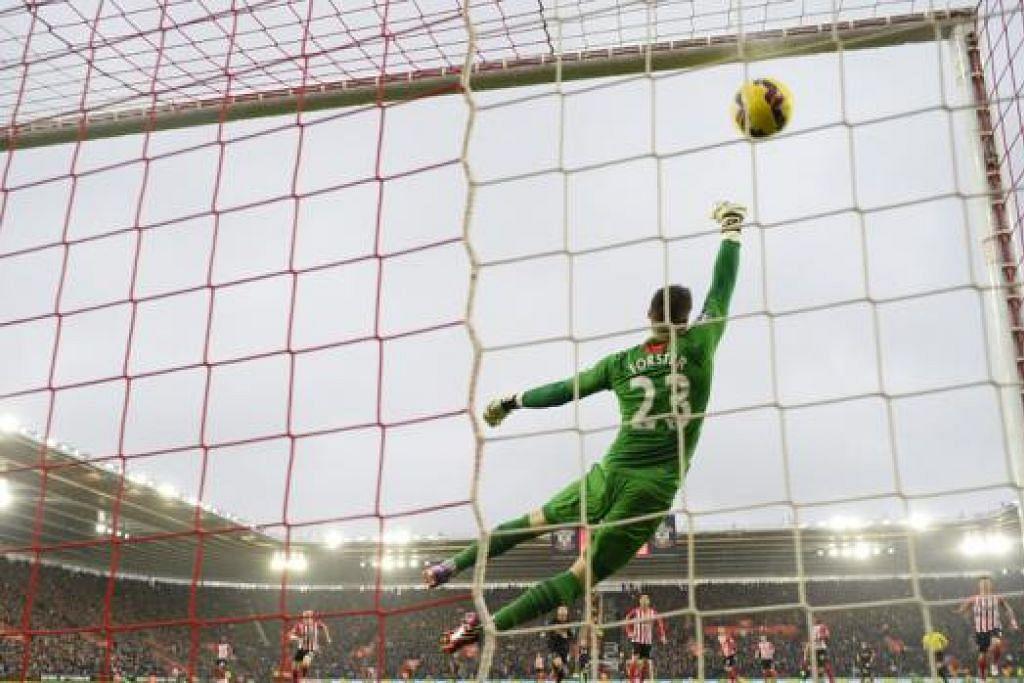 GOL CANTIK: Philippe Coutinho (jersi hitam, terlindung) membuat percubaan cantik dari jarak jauh ke penjuru gawang melepasi jangkauan Fraser Forster bagi gol pembukaan Liverpool. - Foto REUTERS