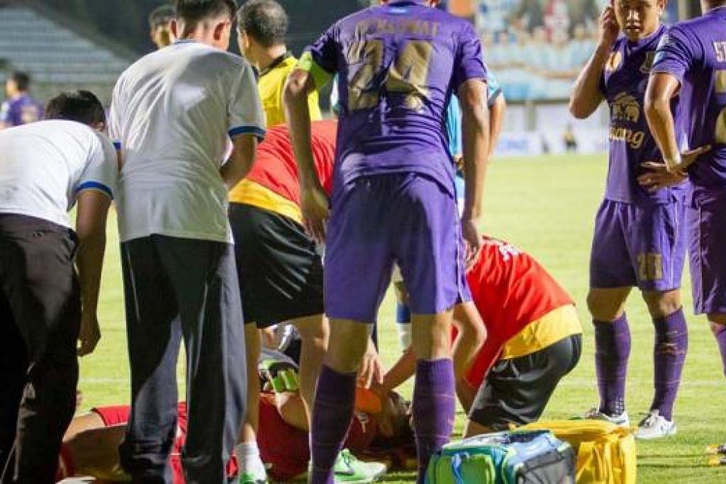 ADEGAN CEMAS: Hassan dikerumuni rakan sepasukan dan kru perubatan selepas mengalami kecederaan dalam perlawanan Liga Perdana Thailand Sabtu lalu. - Foto FANS OF ARMY UNITED