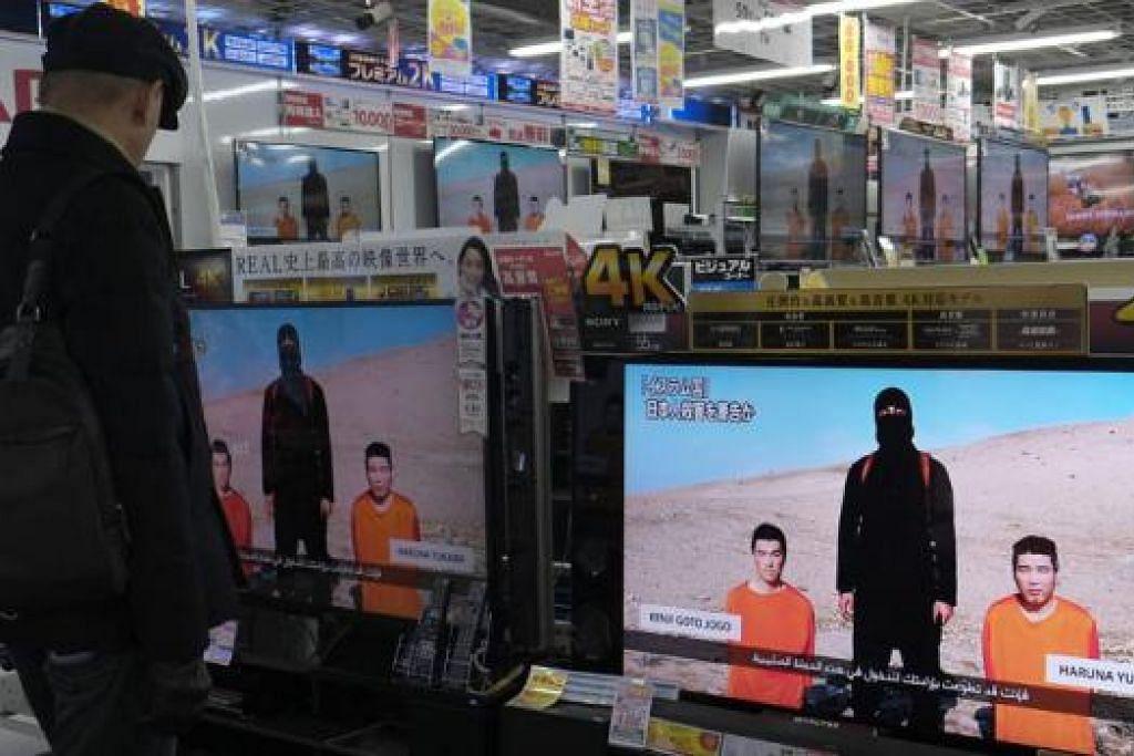 KEKEJAMAN BERTERUSAN: Lelaki di Tokyo, Jepun, menonton siaran berita yang menampilkan video militan IS dengan tawanan Jepun dahulu. - Foto REUTERS