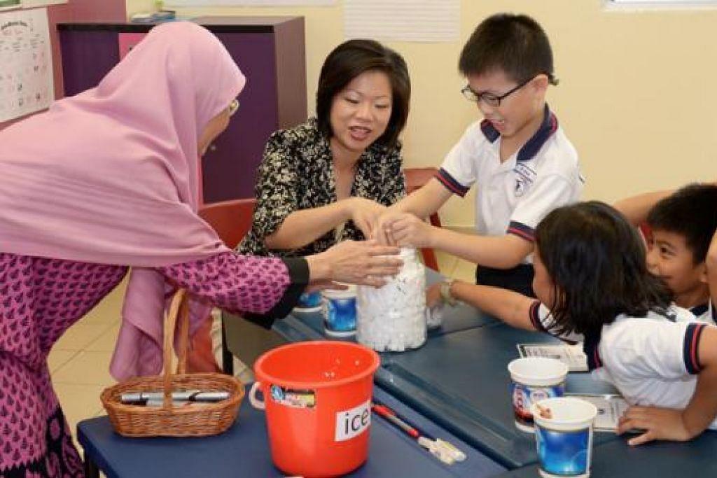 TINJAU PROGRAM: Cik Sim Ann mengunjungi kelas yang dikendalikan pembantu guru, Cik Tutek, bagi murid-murid disleksia. - Foto THE STRAITS TIMES