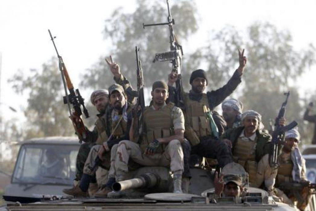 MEMERANGI IS: Tentera Iraq dan pejuang Syiah duduk di atas kereta kebal di wilayah Salahuddin semalam. Mereka telah melancarkan serangan ke atas kubu kuat militan Negara Islam di Tikrit, utara Baghdad. - Foto REUTERS