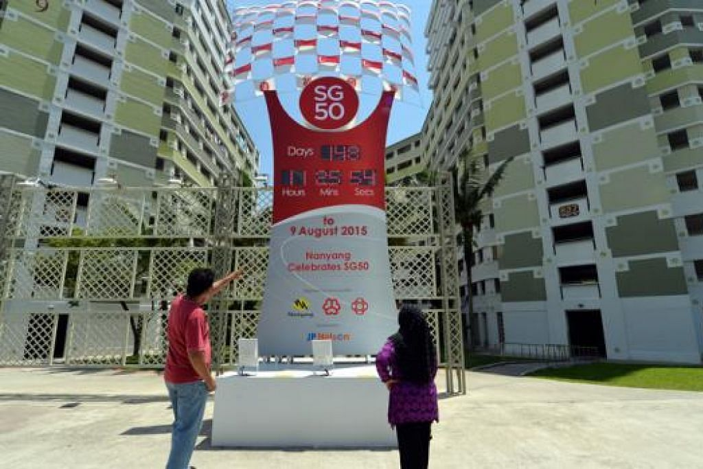 GHAIRAH: Cik Rose bersama suaminya yang tinggal di Blok 839, begitu ghairah apabila melihat Countdown SG50 yang terpacak di hadapan kawasan tersebut di antara Blok 837 dengan 839, Jurong West Street 81. – Foto M.O. SALLEH