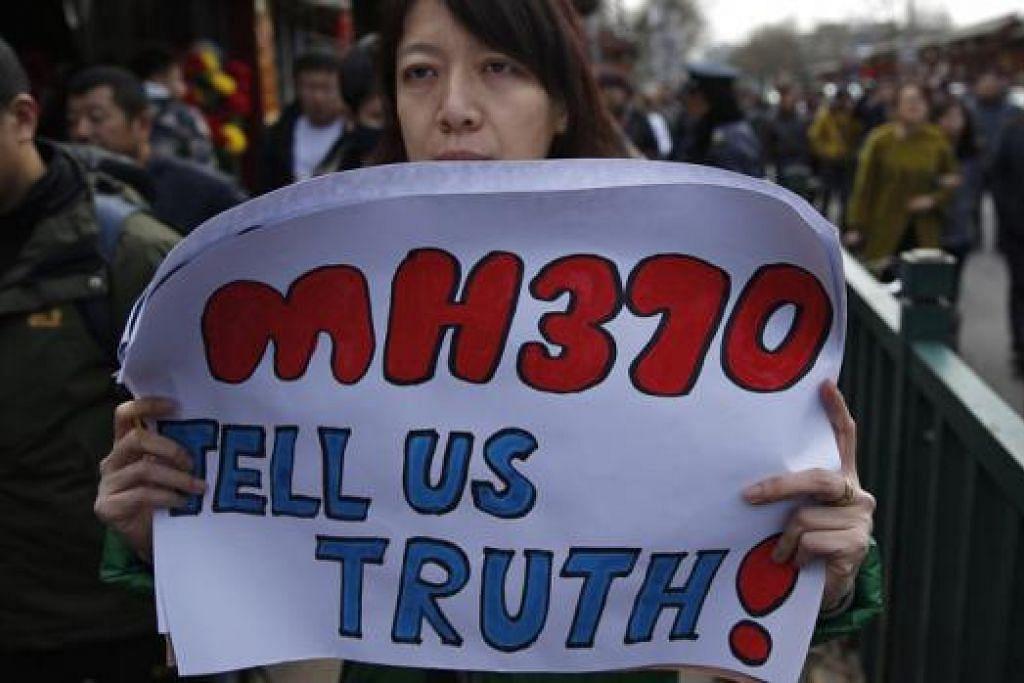 TERUS MENDESAK: Seorang wanita yang suaminya antara penumpang pesawat MH370, memegang sepanduk di luar Kuil Yonghegong Lama selepas perhimpunan waris penumpang di Beijing, semalam. - Foto REUTERS