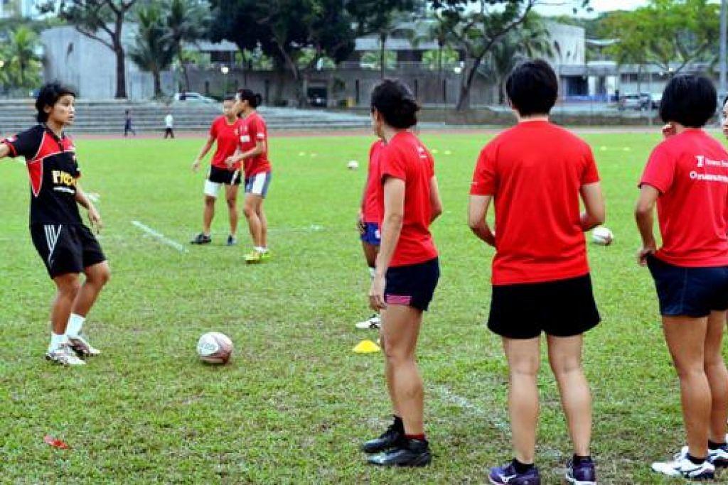 BERI TUNJUK AJAR: Penolong jurulatih Wang Shao-Ing (jersi hitam) memberi arahan kepada pemain nasional cara menjalankan latihan dalam sesi di Stadium Yio Chu Kang lewat petang semalam. - Foto KHALID BABA