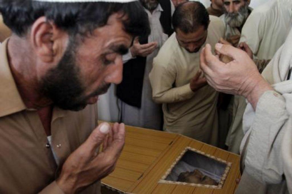 SASARAN PENGGANAS: Beberapa lelaki berdoa dekat keranda Encik Samiullah Afridi, peguam yang ditembak lelaki bersenjata yang tidak dikenali pada Selalu lalu. Militan Pakistan Jendullah, iaitu sebuah kumpulan serpihan Taleban, mengaku bertanggungjawab ke atas pembunuhan itu. - Foto REUTERS