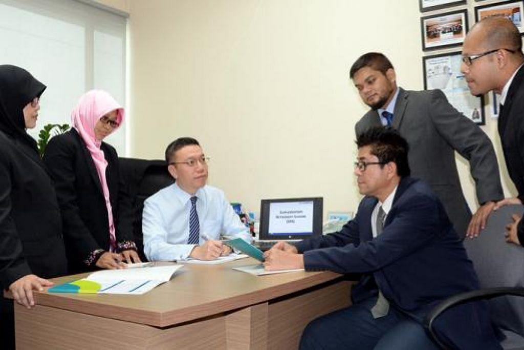 BERPANDANGAN JAUH: Ketua Pegawai Eksekutif (CEO) SingCapital Pte Ltd, Encik Alfred Chia (tiga dari kiri), bersama barisan konsultan kewangan yang dapat membantu masyarakat Melayu khususnya, (dari kiri) Cik Aryati Daud, Cik Noraini Suparman, Encik Abdul Malek Mohamed Yusoff, Encik Rizal Bahri Mohd Tahir dan Encik Ayob Ghani (duduk). - Foto JOHARI RAHMAT