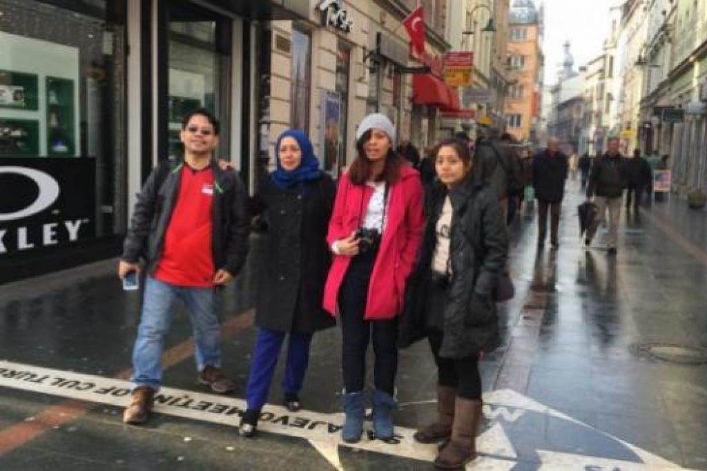 TITIK PERTEMUAN: Penulis (bertudung) dan keluarga melangkah garisan yang dikatakan kawasan pertemuan tamadun Islam dan Barat di pasar Bašcaršija. Tulisan pada garisan itu bermaksud 'Pertemuan Dua Budaya di Sarajevo'.