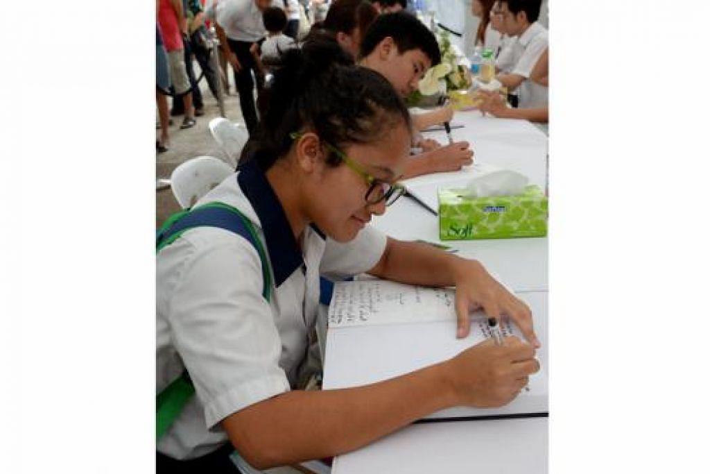 SUARA PELAJAR: Nur Amira Ahmad Zamil, pelajar Sekolah Menengah Geylang Methodist, tidak mahu melepaskan peluang menulis ucapan kepada mendiang Encik Lee semasa di tapak masyarakat di Bedok Town Centre. – Foto TUKIMAN WARJI