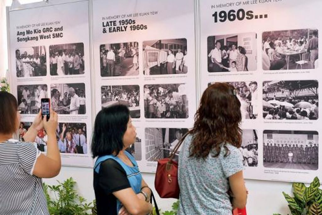 KENANGAN: Orang ramai menatap gambar-gambar lama mendiang Encik Lee Kuan Yew di Ang Mo Kio Central Stage @ Ang Mo Kio Town Centre, salah satu tapak masyarakat bagi orang ramai memberi penghormatan kepada Encik Lee. – Foto KHALID BABA