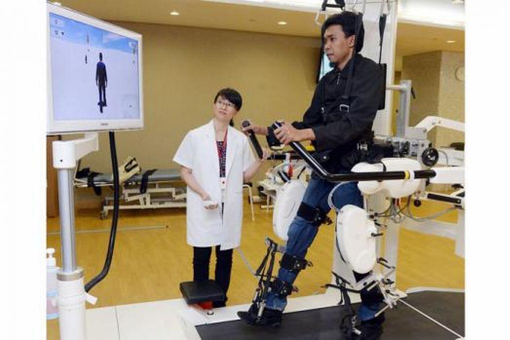 CERAHKAN MASA DEPAN: Mesin Lokomat ini yang sedang dikendalikan Cik Sharon Sew (kiri) telah banyak membantu Encik Rasherman mengingatkannya cara berjalan selain menguatkan ototnya juga. - Foto TAUFIK A. KADER