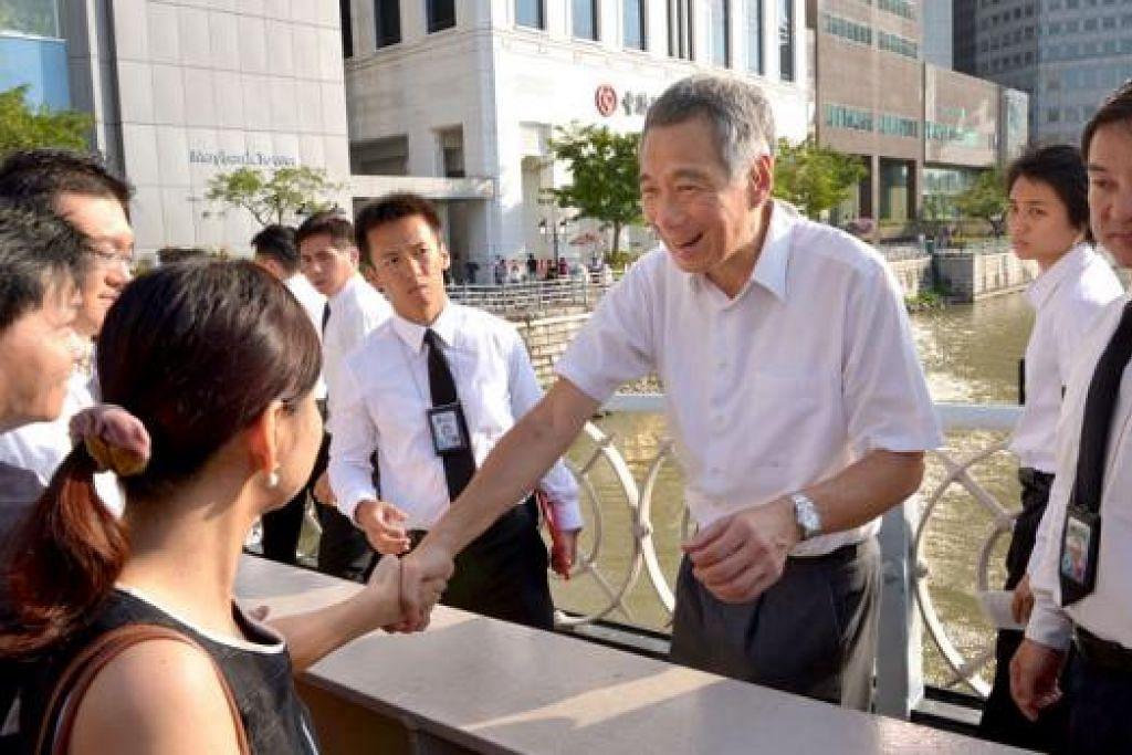 TEMUI RAKYAT: Perdana Menteri Lee Hsien Loong meluangkan masa menemui orang ramai yang sedang beratur di Jambatan Cavenagh semalam. – Foto THE STRAITS TIMES